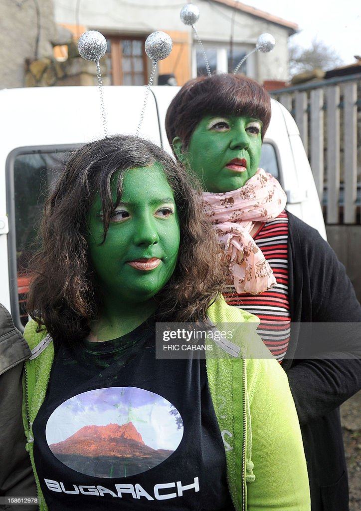 Two people with her faces painted in green walk in the streets of the French southwestern village of Bugarach, on December 21, 2012, near the 1,231 meter high peak of Bugarach - one of the few places on Earth some believe will be spared when the world allegedly ends today according to claims regarding the ancient Mayan calendar. French authorities have pleaded with New Age fanatics, sightseers and media crews not to converge on the tiny village. AFP PHOTO / ERIC CABANIS