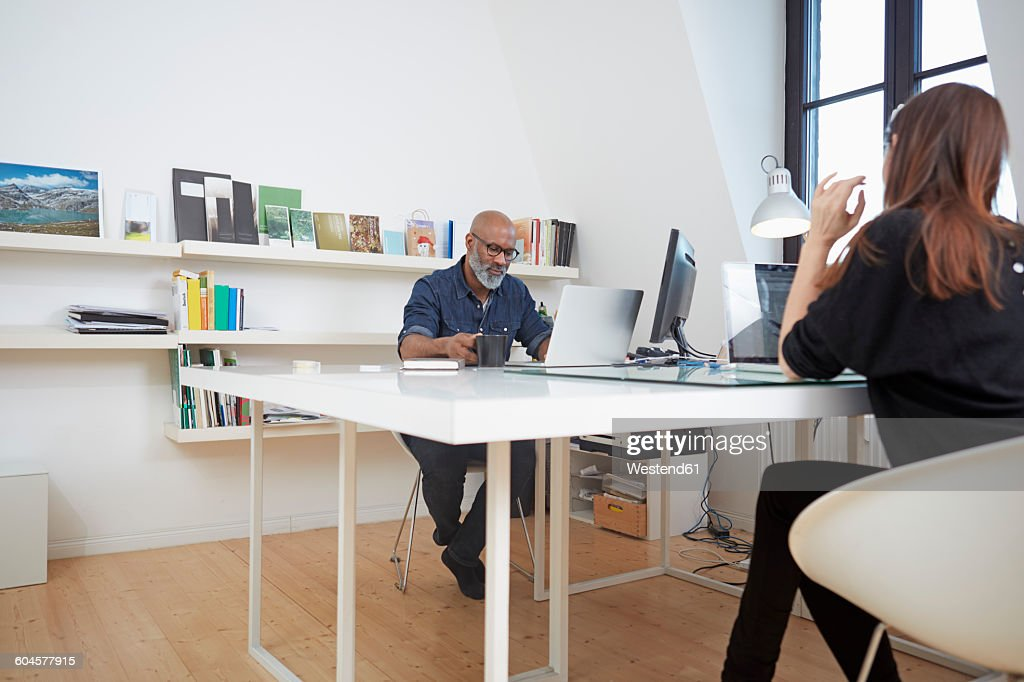 Two people working at desk in an office