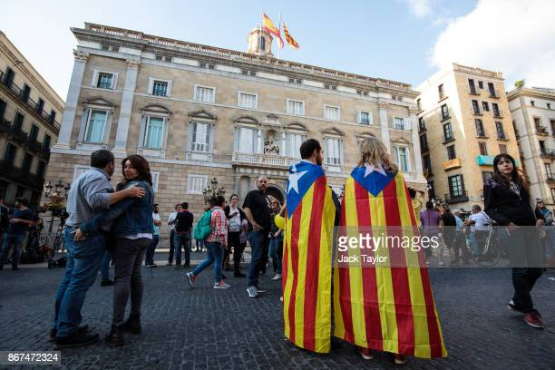 Two people wrapped in the Catalan independence flag gather outside the Catalan Government building the Palau de la Generalitat on October 28 2017 in...
