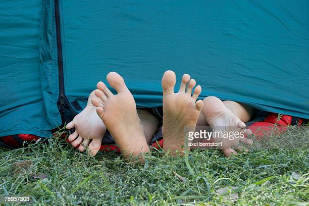 Two people's feet sticking out of tent door.