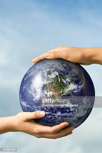 Two people's hands supporting one ball