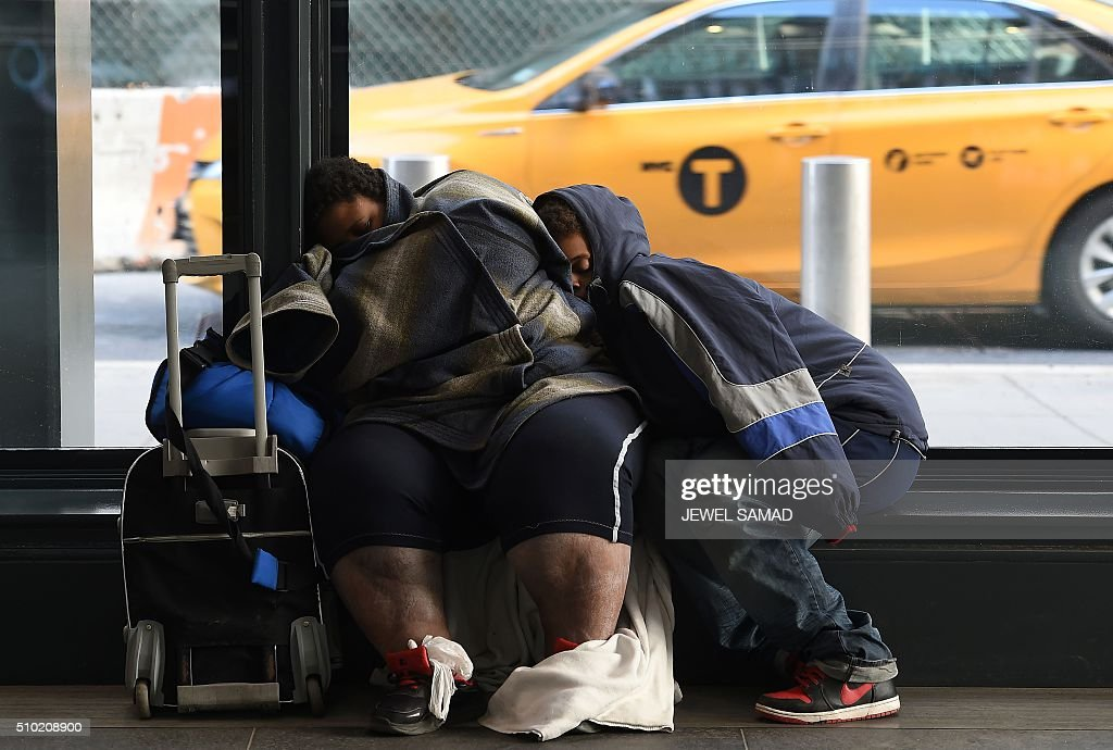 Two person nap inside a subway station during a cold morning in downtown Manhattan, New York, on February 14, 2016. / AFP / Jewel Samad