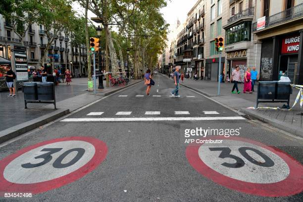 Two persons cross a street on the Rambla boulevard on August 18 2017 a day after a van ploughed into the crowd killing 13 persons and injuring over...