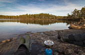 Two persons sitting at the edge of lake making coffe on a camp stove, with pine forest reflected in the lake in the wilderness of Norway