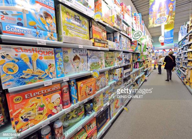 Two persons walk past the shelves of La Grande Recre toys departement store in the French northern city of BruaylaBuissiere on November 20 2010 As...