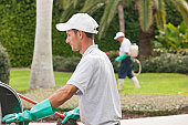 Two pest control technicians working in a lawn environment