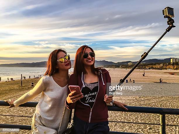 Santa Monica Ca January 22 2015 Two Philippine tourists take a friend selfie with a selfie stick and GoPro camera on the Santa Monica pier