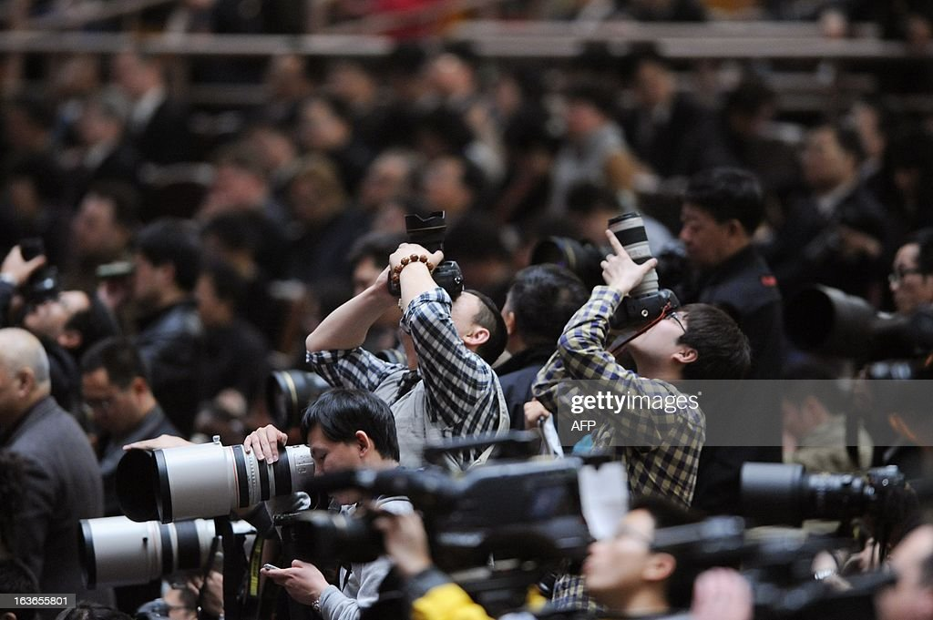Two photographers take photographs during the 12th National People's Congress (NPC) at the Great Hall of the People in Beijing on March 14, 2013. China's parliament named Xi Jinping as president on March 14, four months after he took charge of the Communist Party with pledges of reform that have raised hopes but so far yielded little change.