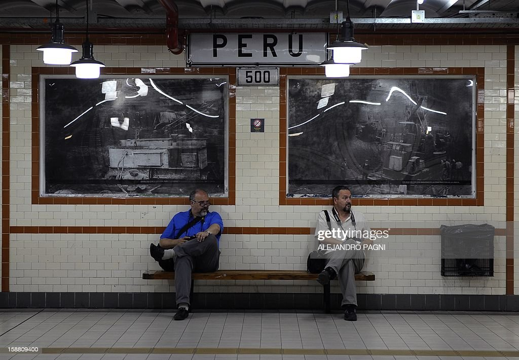 Two photographers wait for the arrival of a train formation of La Brugeoise wagons in the station Peru, part of subway Line A which is expected to be close soon following a decision by city mayor Mauricio Macri to replace the fleet with Chinese-made wagons, in Buenos Aires, on December 29, 2012. Line A was the first subway line to work in the southern hemisphere and its trains are among the ten oldest still working daily. The La Brugeoise wagons were constructed between 1912 and 1919 by La Brugeoise et Nicaise et Delcuve in Belgium. AFP PHOTO / ALEJANDRO PAGNI