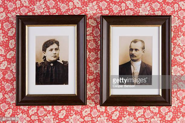 Two photographs hanging on a wallpapered wall
