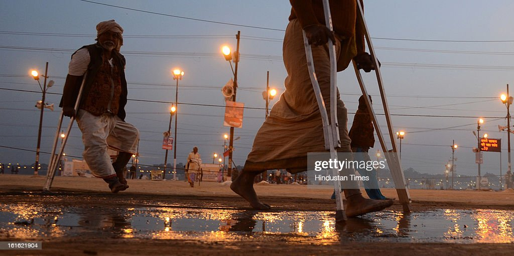 Two physically challenged pilgrims returning after a dip in Sangam waters, in Kumbh Mela area, in Allahabad, India, on Wednesday, February 13, 2013. The mega religious fair is held once in 12 years in Allahabad and the fourth official bathing is set to take place on 'Basant Panchami' on February 15, 2013.