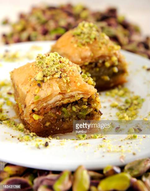Two pieces of Baklava covered in pistachio on a white plate