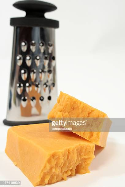 Two pieces of cheese with shredder out of focus in the back