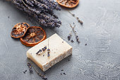 Pece of handmade soap with sprigs of dry lavender and slices of dried orange on a gray background