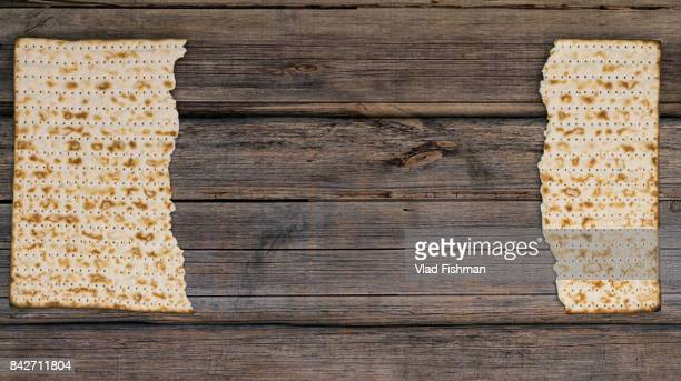 Two pieces of matzah or matza on a vintage wood background with copy space or text space.