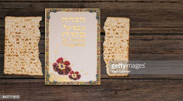 Two pieces of matzah or matza with Passover Haggadah on a vintage wood background with copy space or text space