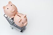 Two Piggy banks in shopping cart isolated on white background.