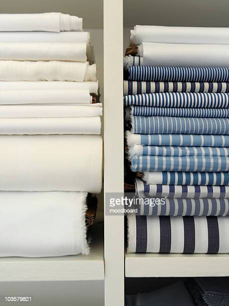 Two piles of cotton towels on shelf