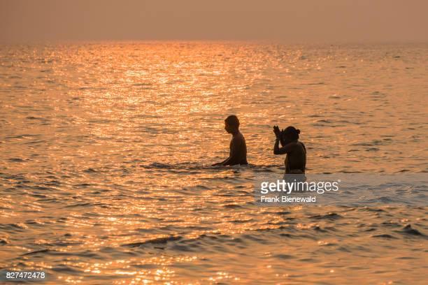 Two pilgrims are praying in the water at Ganga Sagar at sunset celebrating Maghi Purnima festival