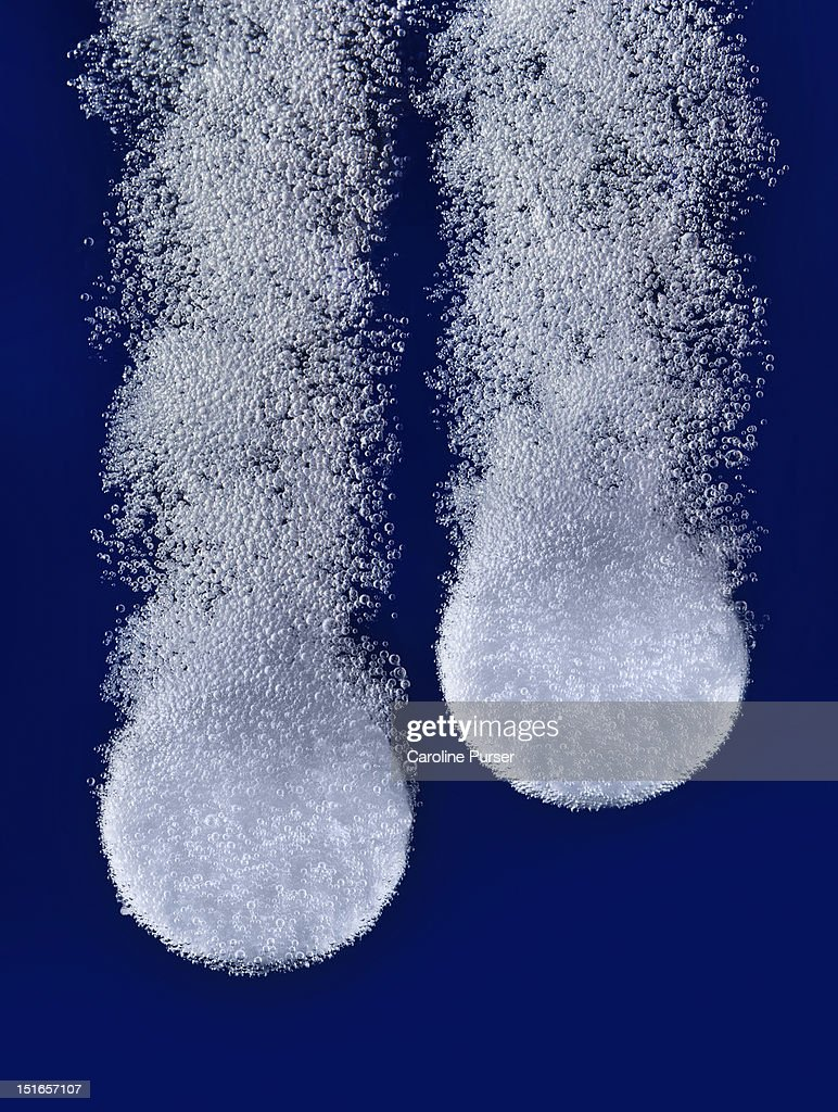 Two pills effervescing in water : Stock Photo