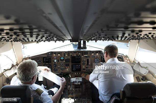 Two pilots in an airplane by the controls