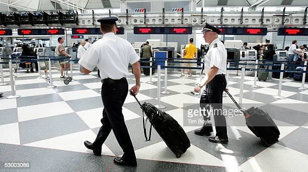 Two pilots walk through the United Airlines terminal at O'Hare International Airport May 31 2005 in Chicago Illinois Aircraft Mechanics Fraternal...