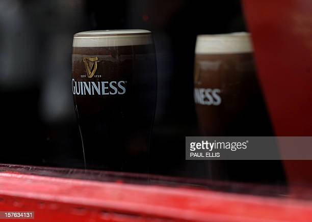 Two pints of Guinness are pictured through a window in The Temple Bar area of Dublin Ireland on May 20 2011 AFP PHOTO / PAUL ELLIS