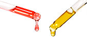 two pipettes with transparent colored liquids and oils drip