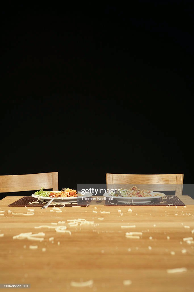 Two plates of pasta on table with bits of pasta covering tabletop : Stock Photo