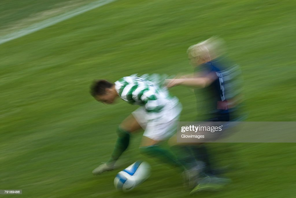 Two players playing soccer in a soccer field : Stock Photo