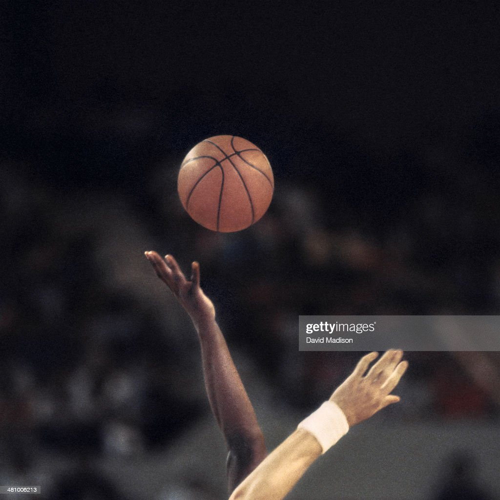Two players reaching for basketball