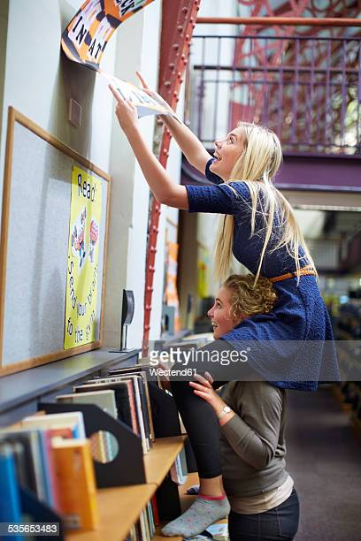 Two playful female students in a library
