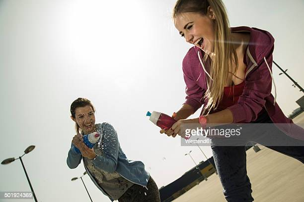 Two playful young women splashing with water bottle