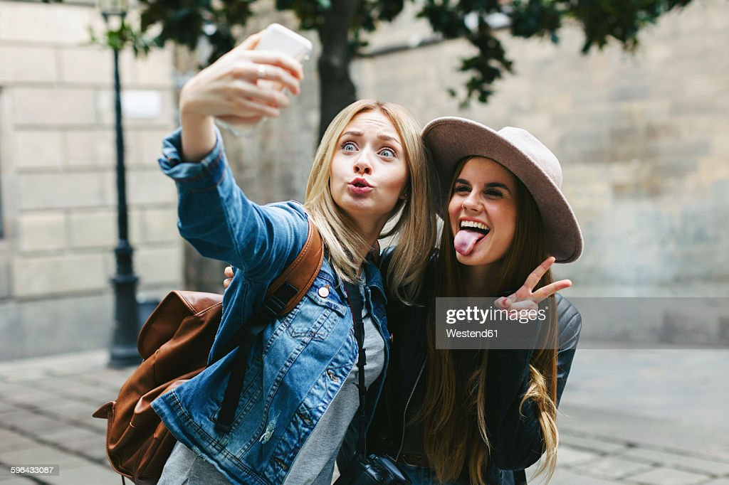 Two playful young women taking a selfie : Stock Photo