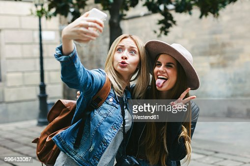 Two playful young women taking a selfie