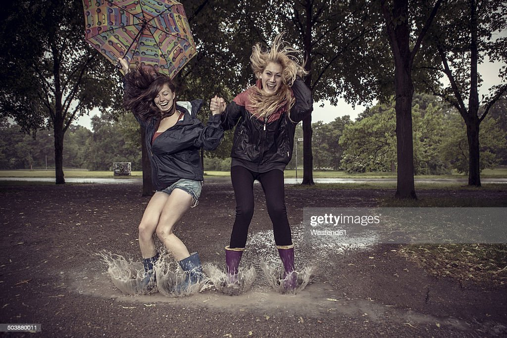 Two playful young women with umbrella jumping in puddle