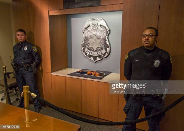 Two police offercers stand guard over the recovered 300yearold Stradivarius violin that was taken from the Milwaukee Symphony Orchestra's...
