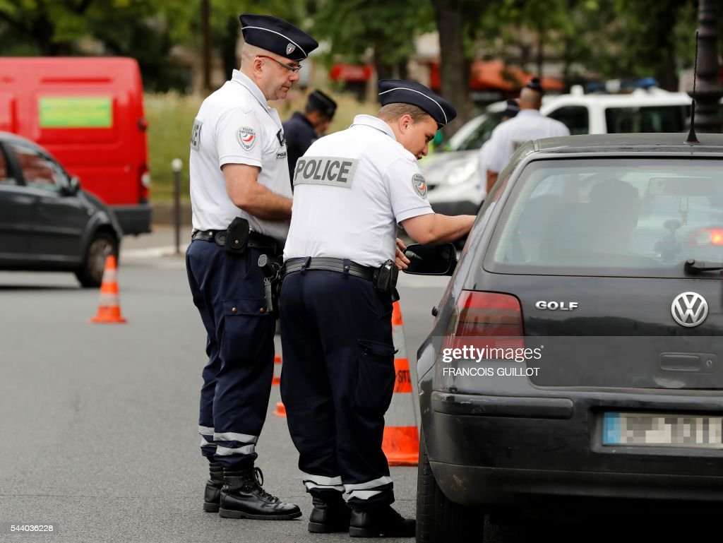 Two police officers control a motorist and his car on July 1, 2016 in Paris as part of the anti-pollution measures aimed at punishing road transports registered before 1997 that are forbidden to be driven during the week. Nearly thirty police officers stood guard on the morning of July 1, in the main squares of Paris to control and raise awareness among the drivers about the new measures concerning road transports adopted by the city and effective from today. Those first controls, mostly to inform and without verbalisation, were organised by the police headquarters and Paris city hall. / AFP / FRANCOIS