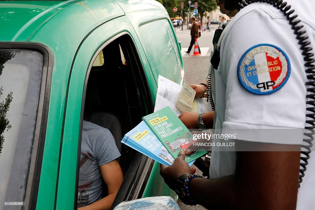 Two police officers give brochures as they control a motorist and his car on July 1, 2016 in Paris as part of the anti-pollution measures aimed at punishing road transports registered before 1997 that are forbidden to be driven during the week. Nearly thirty police officers stood guard on the morning of July 1, in the main squares of Paris to control and raise awareness among the drivers about the new measures concerning road transports adopted by the city and effective from today. Those first controls, mostly to inform and without verbalisation, were organised by the police headquarters and Paris city hall. / AFP / FRANCOIS