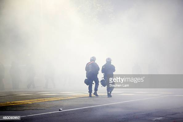 Two police officers in riot gear walk through a cloud of tear gas during a demonstration over recent grand jury decisions in policeinvolved deaths on...