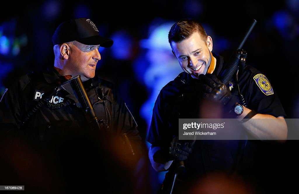 Two police officers laugh while securing the area around Franklin Street on April 19, 2013 in Watertown, Massachusetts. A manhunt for a suspect in the Boston Marathon bombing, Dzhokhar A. Tsarnaev, 19, ended this evening with his capture on a boat parked on a residential property in Watertown, Massachusetts. His brother Tamerlan Tsarnaev, 26, the other suspect, was shot and killed by police early this morning after a car chase and shootout with police. The two men are suspects in the bombings at the Boston Marathon on April 15 that killed three people and wounded at least 170.