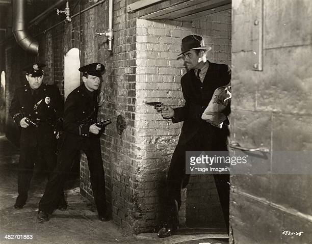 Two police officers lie in wait for a bank robber in a scene from a movie circa 1940