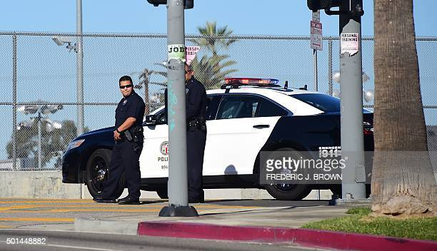 Two police officers stand at their vehicle outside a closed school near downtown Los Angeles on December 15 2015 Los Angeles city officials on...