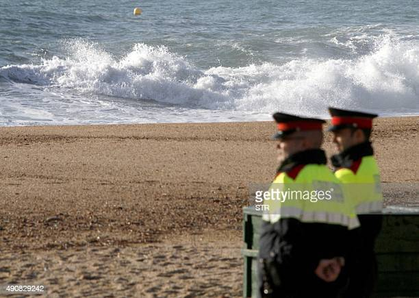 Two police officers stand on the beach of Lloret de Mar northeastern Spain where the drowned bodies of two British women were found on October 1 2015...