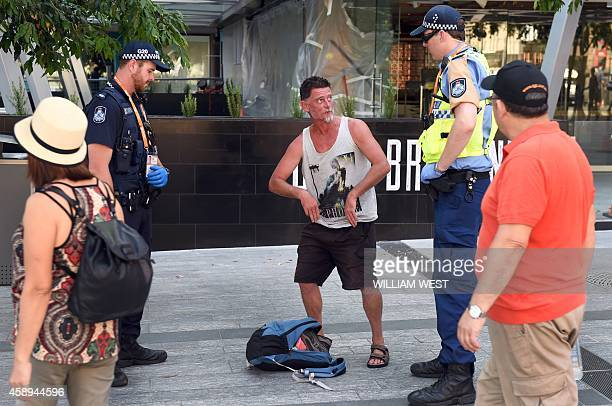 Two policemen check a man's backpack as security intensifies ahead the G20 Leader's Summit in Brisbane on November 14 2014 The G20 Leader's Summit...