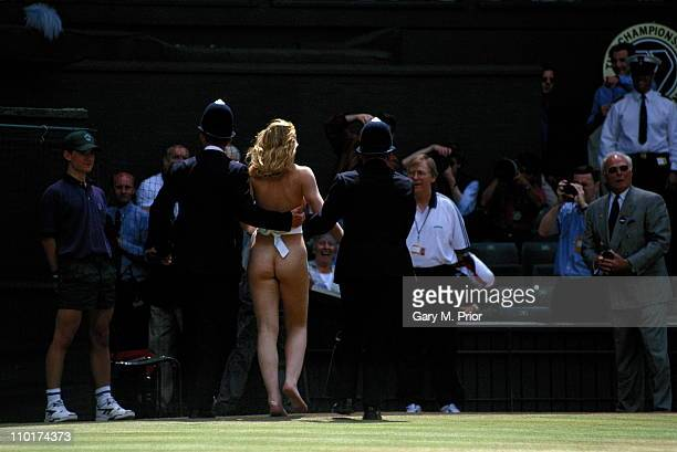 Two policemen escort a streaker away after she had run across Center Court just before the Men's Singles final match between Richard Krajicek of the...