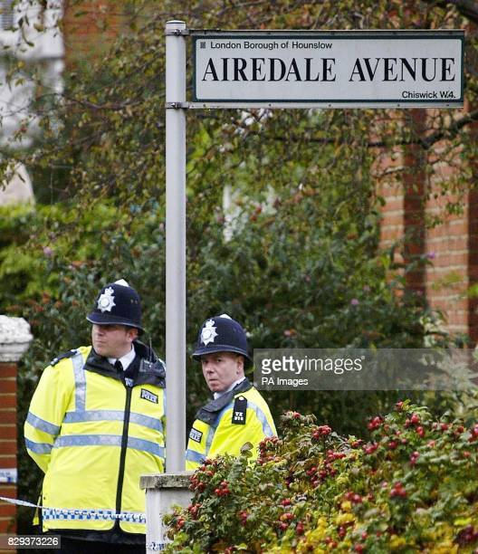 Two policemen guard an area oustide a property on a treelined street among rows of exclusive houses and flats in Airedale Avenue Chiswick west London...