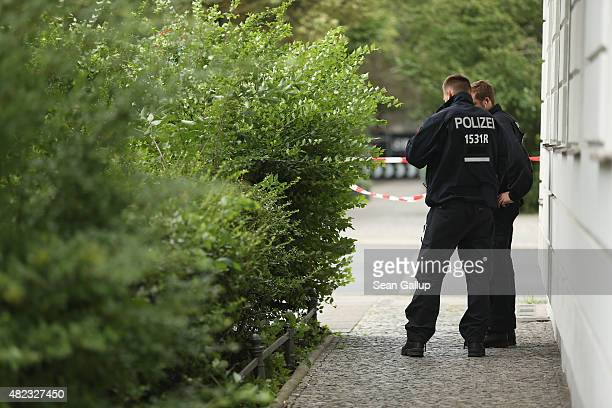 Two policemen stand at the site of a shooting at Olivaerplatz on July 30 2015 in Berlin Germany At approximately 930 pm the day before gunmen opened...