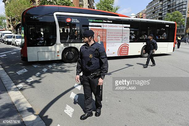 Two policemen stand guard next to a bus carrying students of the Joan Fuster Institute in a bus in Barcelona on April 20 2015 after a student...