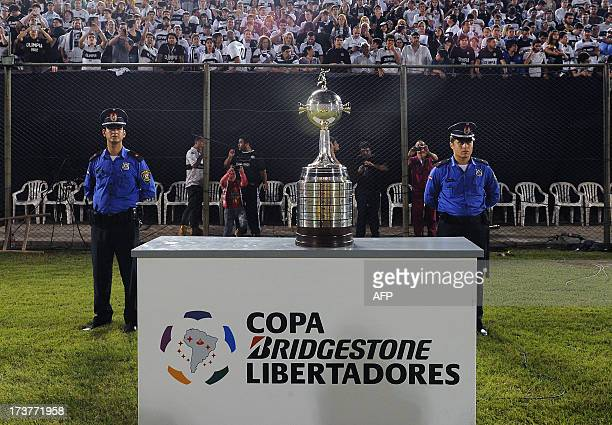 Two policemen stand guard next to the Libertadores Cup trophy before the start of the first leg final between Paraguay's Olimpia and Brazil's...